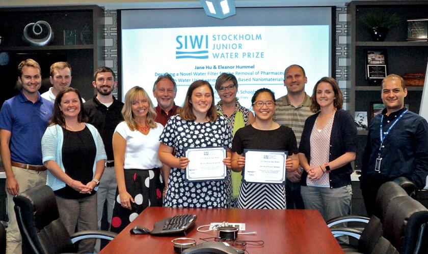 Ellie Hummel and Jane Hu, at center, left and right, respectively, hold their SJWP certificates. Attending the ceremony were Valerie Lucas, representing KY-TN WEA, at Ms. Hummel's left; Kay Sanborn, representing KY/TN AWWA, back row between the prize winners, and Milad Ebrahimi, representing Louisville MSD, far right. Louisville office team members shown include, from left, Tyler Bridges, Nick Gunselman, Shanna Stone, Josh Flanery, Robert Bates, Joe Pavoni, and Adalyn Haney.